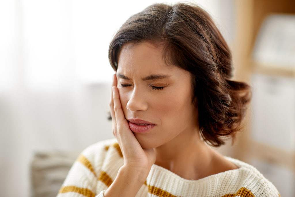unhappy woman suffering from toothache at home