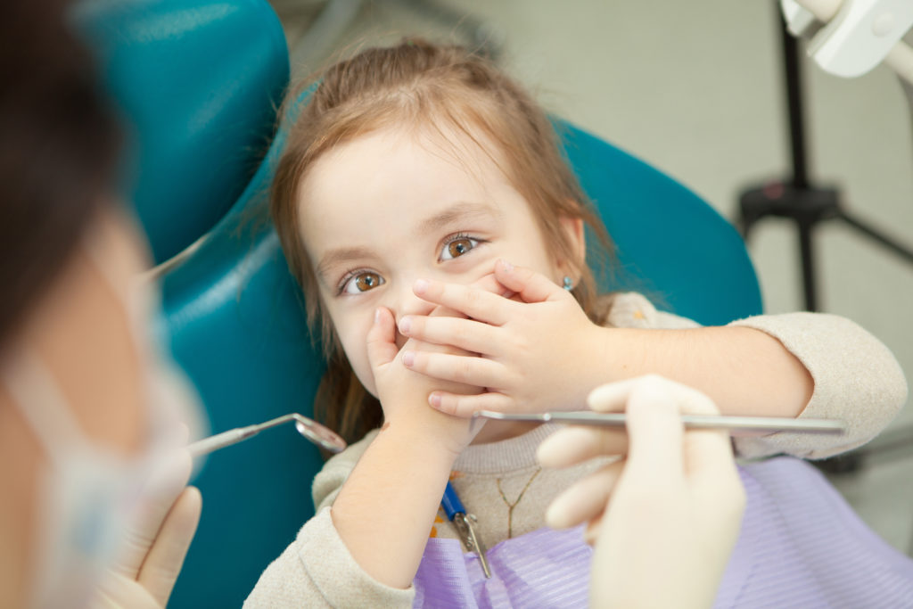 Kid afraid of procedure closes mouth with hands
