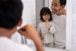 dad and girl brush their teeth together